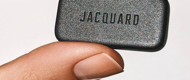 Close up of someone holding jacquard between their thumb and finger