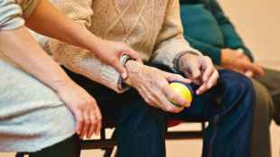 Close up of someone holding the right hand of an elderly person. The elderly person has a yellow ball in their hand.