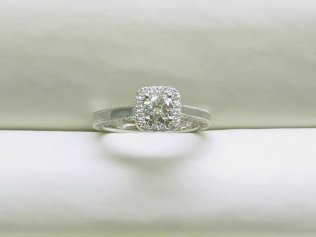 custom engagement ring with a cushion shape halo and a round center diamond