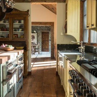 Natural stone, rustic wood, and painted cabinetry make this sunny kitchen a happy place to be.