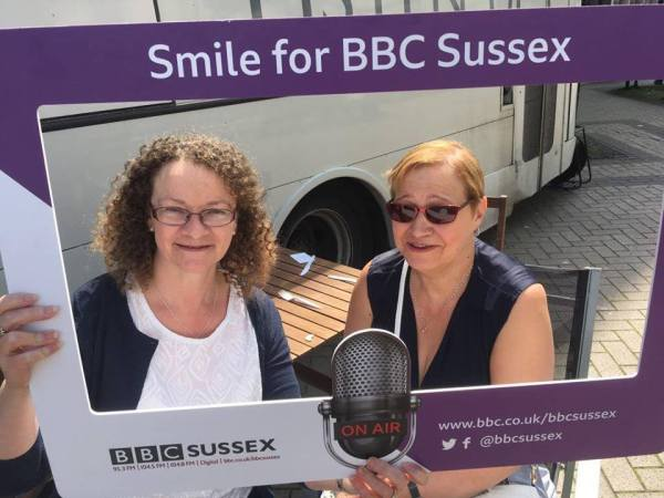 Julie and Volunteer smiling inside BBC Sussex Frame