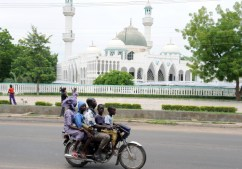 A picture taken on July 28, 2011 shows a public transport motorcylist carrying four passengers driving past a mosque in central Maiduguri, capital of Borno State. A powerful bomb blast targeting soldiers followed by gunfire rocked the troubled Nigerian city of Maiduguri on December 13, 2011 with at least 10 people killed, an official and a hospital source said. Residents claimed soldiers reacted to the bombing by shooting indiscriminately and burning homes, with troops having been accused of such abuses following previous attacks after alleging residents were complicit. A military spokesman denied the accusations. AFP PHOTO / PIUS UTOMI EKPEI (Photo credit should read PIUS UTOMI EKPEI/AFP/Getty Images)