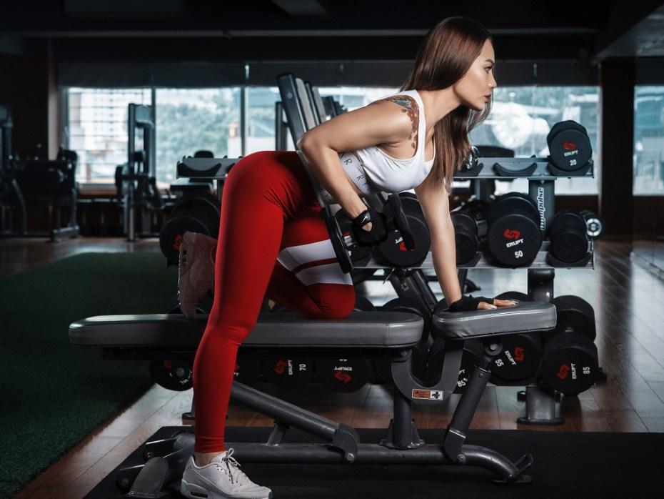 kobieta podnosząca ciężar, siłownia, trening, efekty treningu