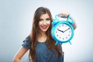 Training New Dental Front Office Team Members Takes Time. A Woman Holds A Clock Displaying The Time it Takes In Training New Dental Front Office Team Members
