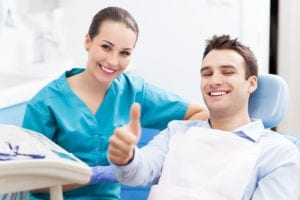 A dental hygienist sits next to a male dental patient giving a thumbs up. Creating the dental hygiene schedule and maintaining the ideal dental hygiene schedule can be accomplished with the Dental Hygiene Schedule Master Class.