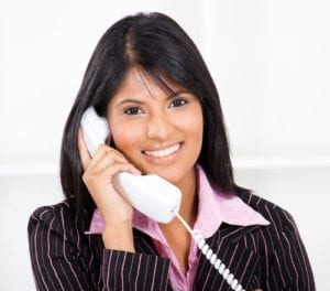A smiling woman answers a dental office telephone. She has great dental office customer service as she focuses only on her patient calling.