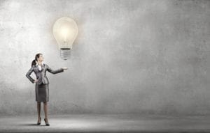 A businesswoman holding a lightbulb showing that she can come up with ideas to handle dental restorative appointments cancelling