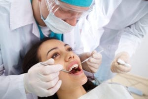A healthy female dental patient is having her dental cleaning. Learning dental hygiene scheduling also requires an understanding of different types of hygiene visits.