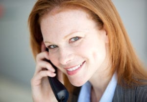 """Building trust with dental patients often starts with """"Hello"""" when dental patients reach out to the dental office for the very first time. A woman is answering the dental office telephone and smiles."""