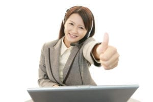 A woman with a headset smiles with a thumbs up as she is improving dental customer service she is having a better day.