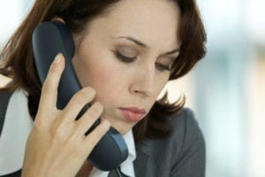 A businesswoman talks on the phone as she is working overdue patient accounts