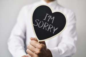 """A man holds a chalkboard heart that says """"I'm sorry"""" to represent apologizing to a dental patient with a complaint."""