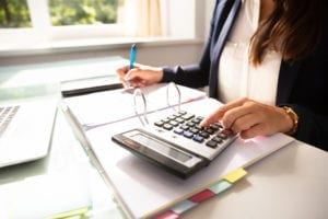 A dental front office team member audits a patient's credit balance as she works on the dental office credit balances.