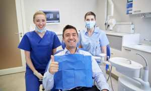 A happy dental patient refers more new patients. Dental office phone training creates happy patients. This happy male dental patient sits in the dental chair . Behind him are the dentist and dental assistant.