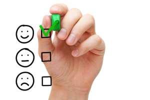 A hand checks a smiley face to represent superior customer service