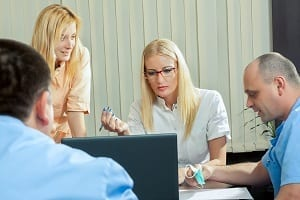 A team of dental workers meet together to discuss business.