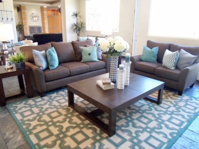 Living room staging with brown and teal accents