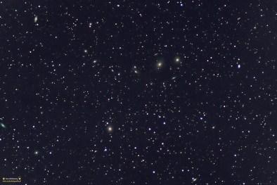 """Łańcuch Markariana. Pentacon 300/4 @f:5 ISO800 25x120 sekund (sumarycznie 50 minut). Montaż EQ5. entacon 300/4 @f:5 ISO800 25x120 sekund (sumarycznie 50 minut). Warunki były naprawdę niezłe, ale muszę się przyznać, że nawet tak krótką ogniskową trochę się namęczyłem żeby wycelować mniej więcej w centrum - dookoła jest tak dużo galaktyk, że trudno było się decydować co zostawiać a co obcinać. Na zdjęciu mniej więcej powyżej środka po prawej stronie widać przesunięty obiekty którym jest asteroida Pallas. W czasie focenia zostałem """"otoczony"""" przez stado dzików - ciśnienie poszło mi maksymalnie, ale jakoś udało się odgonić to towarzystwo... Zdjęcie to minimalnie obcięty pełen kadr - niestety zrobiło się nieco cieplej i żeby wyciągnąć jak najwięcej z fotki trzeba było obrabiać aż do """"wyjścia"""" rozświetleń od wzmacniacza - idzie je usunąć ale nigdy nie jest to bez wpływu na kolor - stąd galaktyczki i gwiazdy z brzegu jadą nieco w stronę """"cyjanu""""."""