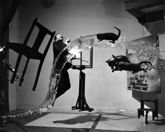 4th House Uranus, 5th House Uranus, 6th House Uranus: black-&-white surrealistic photo of a chair, a man, water flow, a cat and other creatures frozen in the air, all captured by camera.