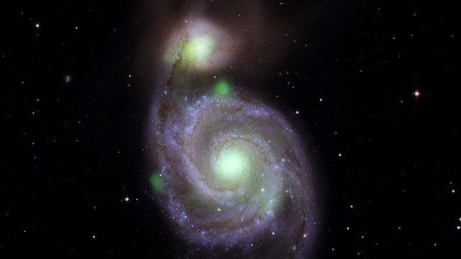 Sumber cahaya hijau terang sinar-X energi tinggi yang dipotret misi NuSTAR yang digabungkan dengan foto pengamatan optik Galaksi Whirlpool dan galaksi M51b pasangannya.  Cahaya hijau terang dari pusat kedua galaksi berasal dari materi di sekitar lubang hitam supermasif. Bintang neutron ultraterang berada di sisi kiri Whirlpool.  Kredit: NASA