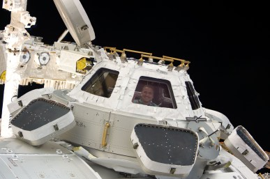 STS-130_George_Zamka_looks_through_the_Cupola