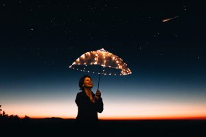 Dame onder beschermende paraplu van licht