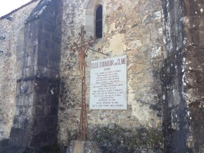The plaque on the outside wall of the church. In the ruined town, only Christ on the cross, Notre-Dame de Lourdes, and [Saint?] Bernadette remained standing.
