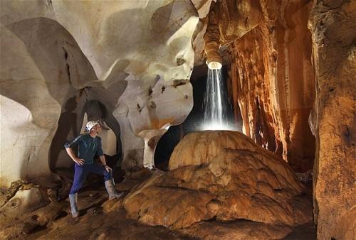 Sarawak, Borneo - Un explorador admira esta ducha de agua formada bajo la cueva Racer.