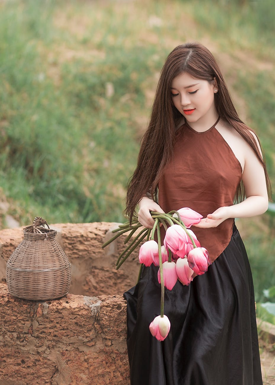 woman holding pink tulips