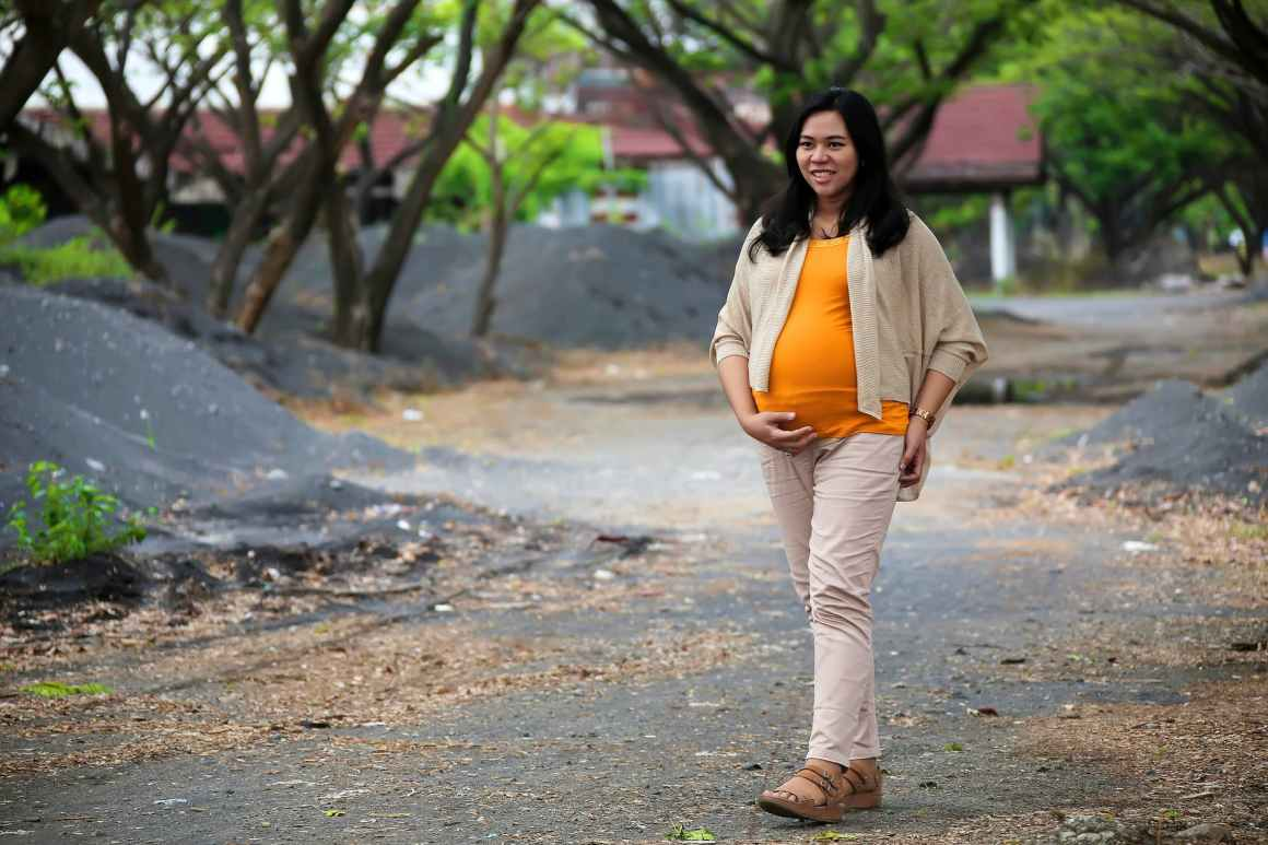 photo of pregnant woman walking on pathway
