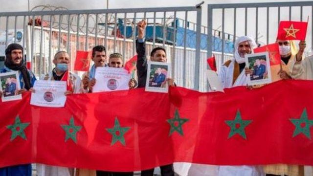 اشخاص يحملون أعلاما مغربية