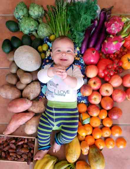 Baby surrounded by fresh veggies and a grocery haul