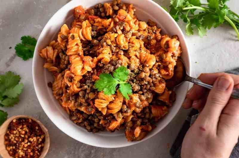 Easy lentil bologese pasta in a bowl being eaten