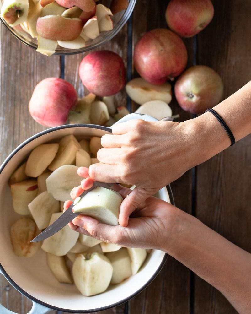 Hand peeling apples in a pot