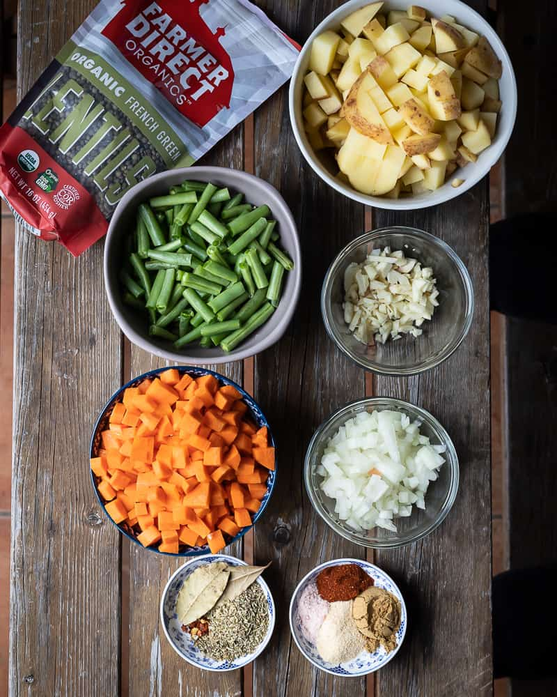 fresh diced veggies on a wooden table for lentil stew