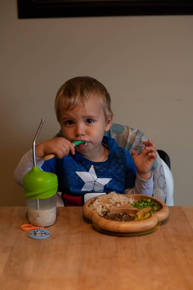 toddler eating lunch at a wooden table