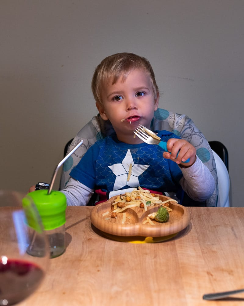 child sitting at a table eating dinner