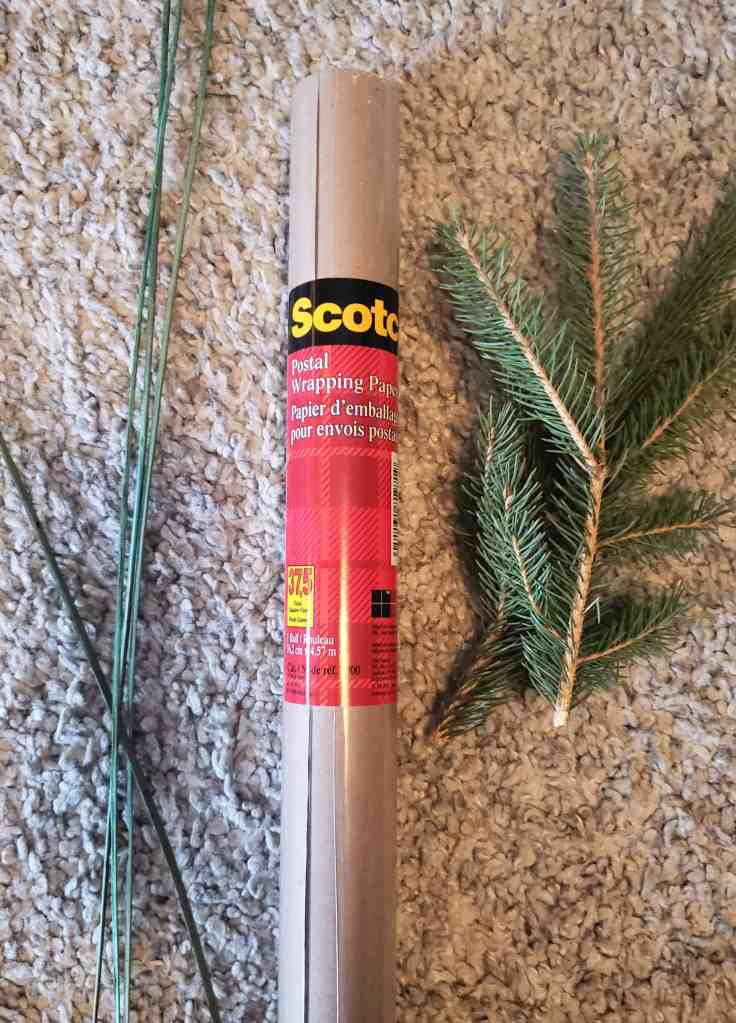 Roll of postal wrapping paper on a carpet surrounded by pine and branches for decorating