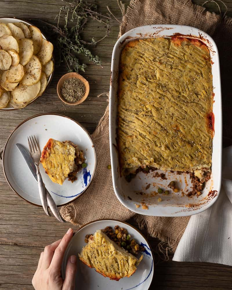 top view of vegan shepherd pie being eaten with full plates and roasted potatoes on the table