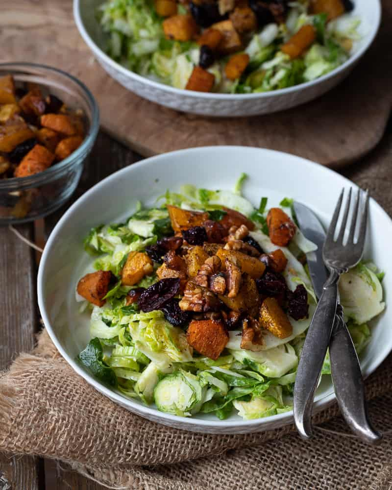 Plate full of salad topped with squash and walnuts on a wodden table surrounded by bowls