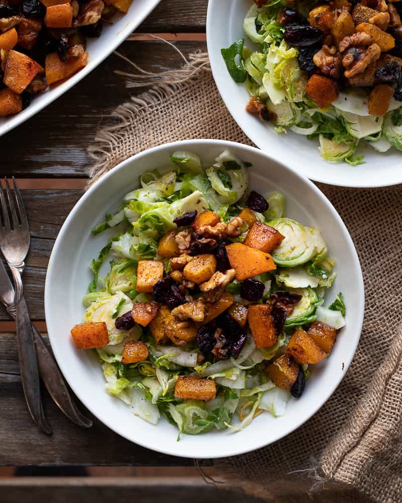 Bowl of brussel sprout salad topped with squash and cranberries on a wooden table