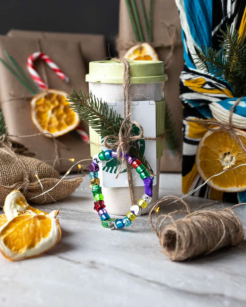 Resuable mug decorated with twine, a coffee card and a bead bracelet surrounded by other presents wrapped in recycled paper