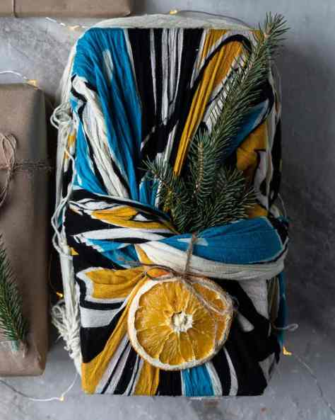 present wrapped in a scarf and decorated with dried fruit