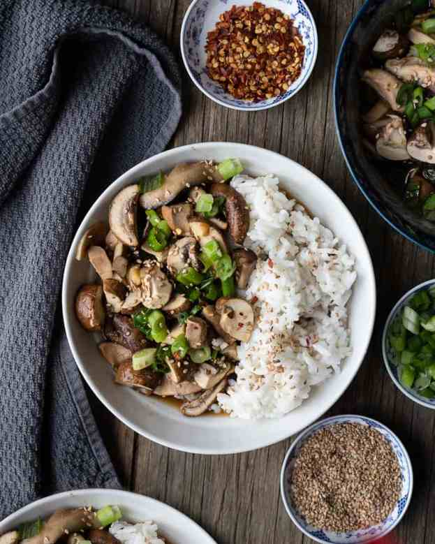 Bowl of brown and portabello mushrooms served with rice and green onions
