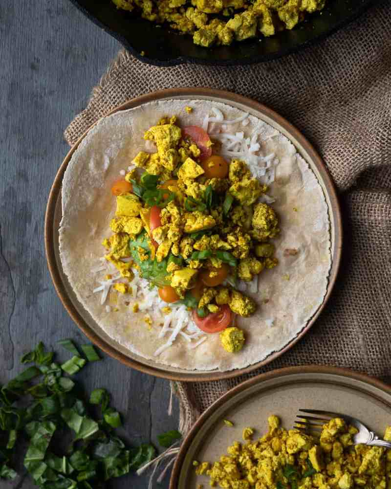 Birds eye view of a a open face wrap with tofu scramble and veggies on the