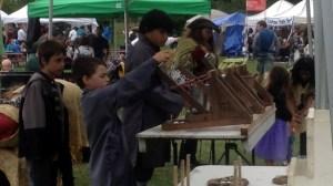 Atado Kids shooting toy catapults at the Royal Medieval Faire