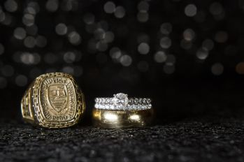 Bride and Groom's wedding bands with engagement and class rings.
