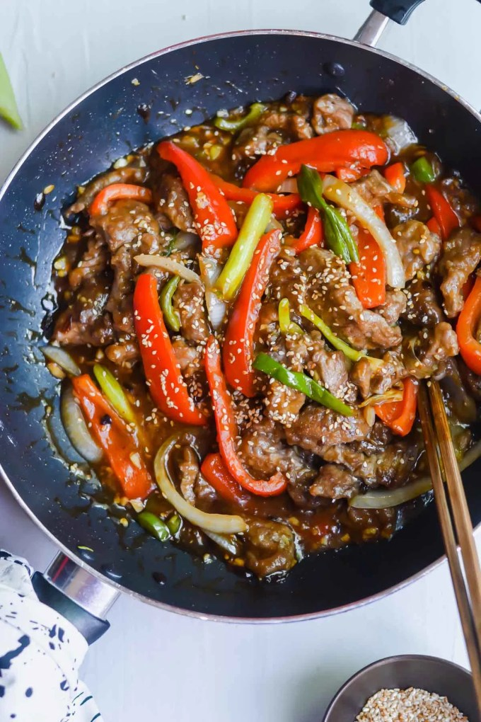 Szechuan beef close up with red peppers and onions