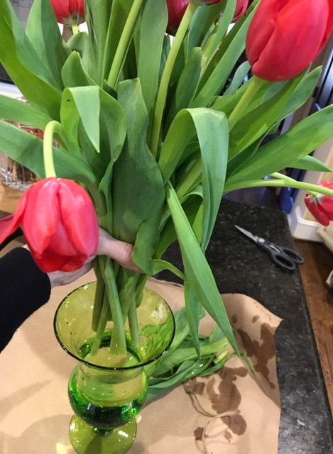 A bunch of tulips being put in a green vase.