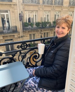 Sue sipping coffee on the balcony in Paris